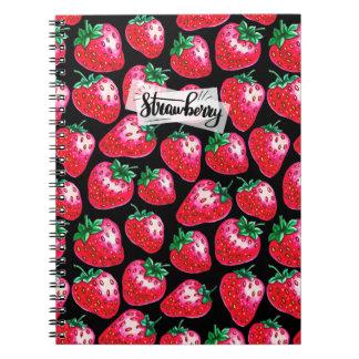 Fresa roja en fondo negro cuaderno