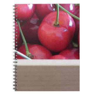 Frontera de cerezas frescas en fondo de madera cuaderno