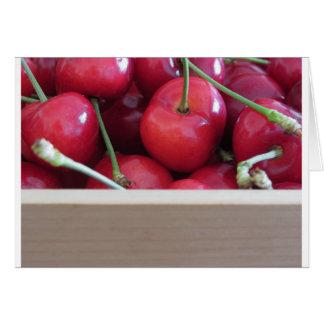 Frontera de cerezas frescas en fondo de madera tarjeta