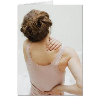 Frotamiento de la mujer que duele detrás tarjeta de felicitación