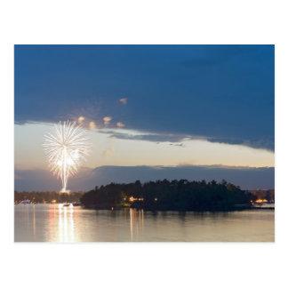 Fuegos artificiales en la oscuridad sobre el lago postal