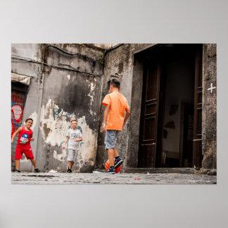 Fútbol del juego de los niños en un callejón de póster