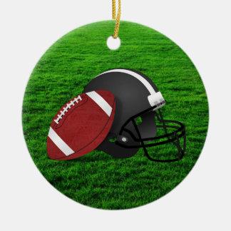 Fútbol y casco en el ornamento de la hierba adorno navideño redondo de cerámica