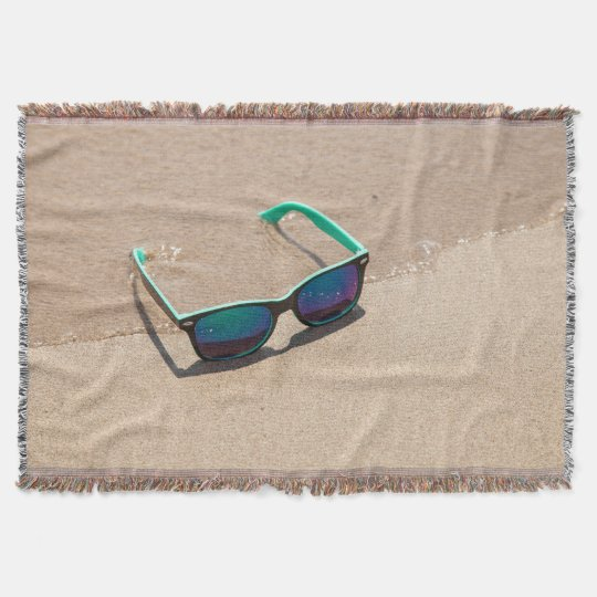 Gafas de sol en la manta del tiro de la playa