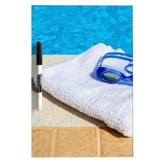 Gafas y toalla de la natación cerca de la piscina pizarra blanca