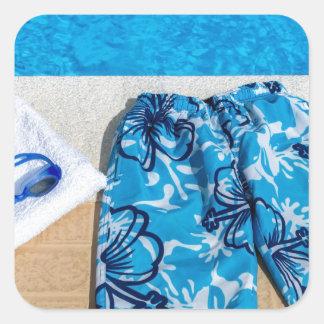 Gafas y toalla de los troncos de natación en la pegatina cuadrada
