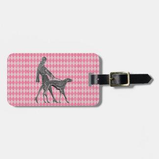 Galgo de la mujer y etiqueta rosada del equipaje
