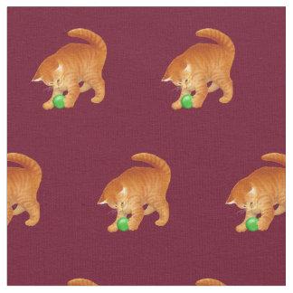 Gato anaranjado del gatito que juega con la tela