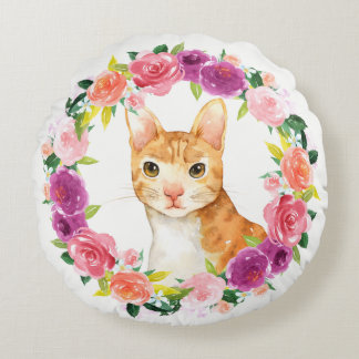 Gato de Tabby anaranjado con la almohada floral de