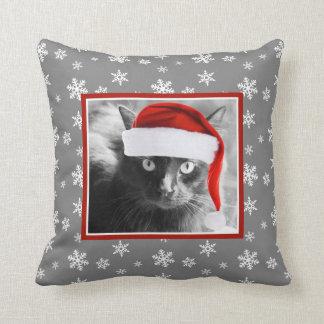 Gato del navidad en la almohada gris con los copos