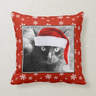 Gato del navidad en la almohada roja con los copos
