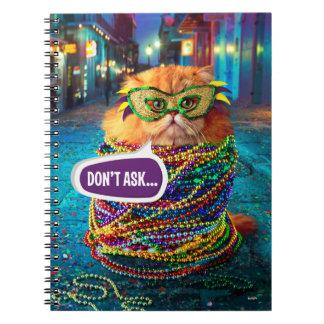 Gato divertido con las gotas coloridas en el cuaderno