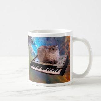 Gato en un teclado en espacio taza de café