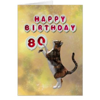 Gato juguetón y 80.os globos del feliz cumpleaños tarjeta de felicitación