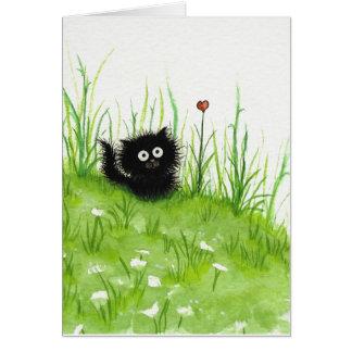 Gato negro borroso por la tarjeta en blanco de