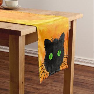 Gato negro del peekaboo lindo en el naranja de camino de mesa