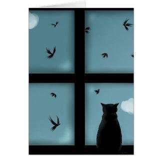Gato negro que considera hacia fuera la ventana el tarjetón