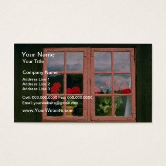 Geranios violetas en la ventana de un tradicional tarjeta de visita