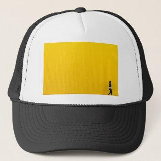 Gorra De Camionero Chica que camina contra la pared amarilla enorme
