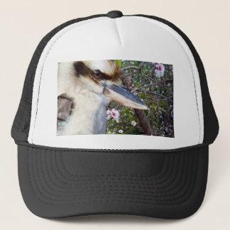 Gorra De Camionero Kookaburra al lado del árbol del flor,