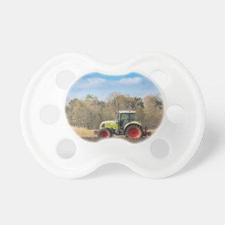 Granjero en el tractor que ara el suelo arenoso en chupete