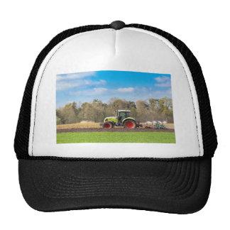 Granjero en el tractor que ara el suelo arenoso en gorras de camionero