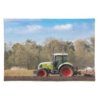 Granjero en el tractor que ara el suelo arenoso en manteles individuales