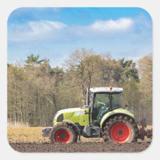 Granjero en el tractor que ara el suelo arenoso en pegatina cuadrada