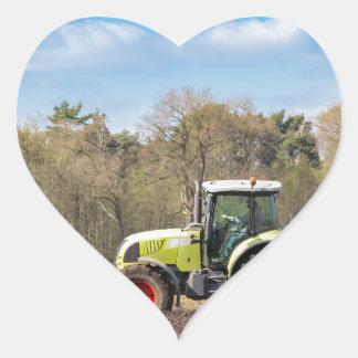 Granjero en el tractor que ara el suelo arenoso en pegatina en forma de corazón