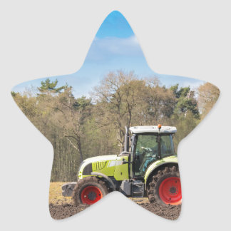 Granjero en el tractor que ara el suelo arenoso en pegatina en forma de estrella