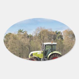 Granjero en el tractor que ara el suelo arenoso en pegatina ovalada