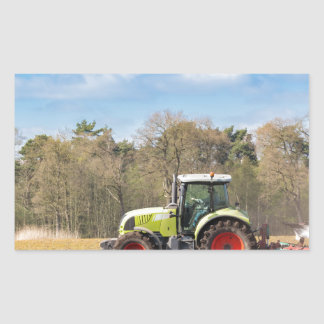 Granjero en el tractor que ara el suelo arenoso en pegatina rectangular