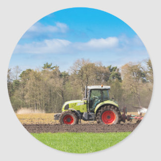 Granjero en el tractor que ara el suelo arenoso en pegatina redonda