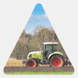 Granjero en el tractor que ara el suelo arenoso en pegatina triangular