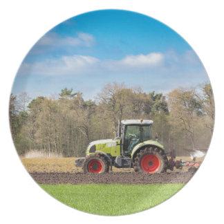 Granjero en el tractor que ara el suelo arenoso en plato