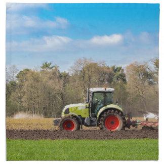 Granjero en el tractor que ara el suelo arenoso en servilleta
