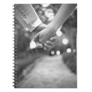 Groom holding hands with bride black and white libreta
