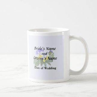Grupo de pensamientos amarillos y púrpuras que taza de café