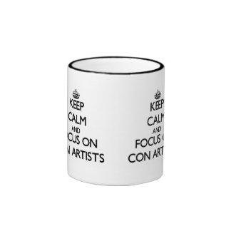 Guarde la calma y el foco en artistas de estafa tazas de café