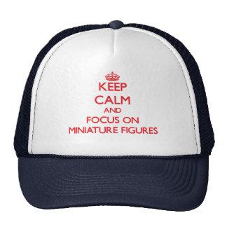 Guarde la calma y el foco en figuras miniatura gorras de camionero