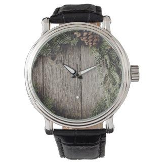 Guirnalda del navidad con el fondo de madera reloj de pulsera