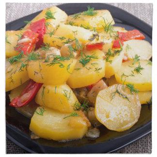 Guisado de patatas con la cebolla, el paprika y el servilleta de tela