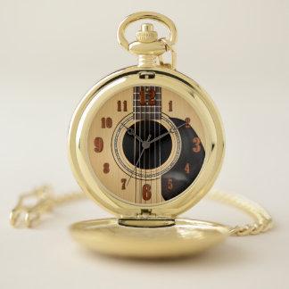 Guitarra acústica con el reloj de bolsillo de los