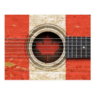 Guitarra acústica vieja con la bandera canadiense postal