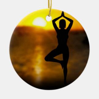 Hembra de la yoga por el océano en el ornamento de adorno navideño redondo de cerámica