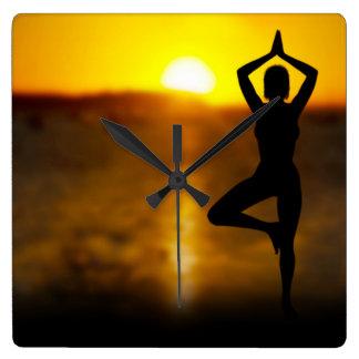 Hembra de la yoga por el océano en el reloj de