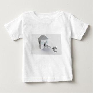 Hogar dominante, agente inmobiliario, vendiendo camiseta de bebé