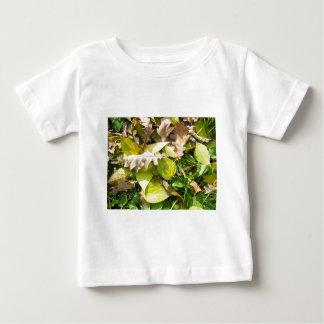 Hojas de otoño caidas en césped de la hierba verde camiseta de bebé
