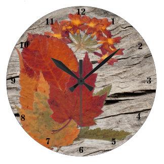 Hojas y flores de otoño en el reloj de madera de l