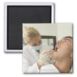 Hombre de examen del dentista de sexo femenino imanes